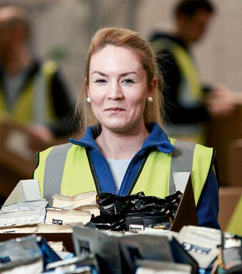 Happy female Speedpak staff member with coffee packs